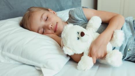 Mädchen-Schläft-Und-Umarmt-Teddybär-In-Einem-Bett
