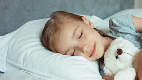 Girl-Sleeping-In-A-Bed-With-Teddy-Bear-And-Smiling-And-Wakes-Up