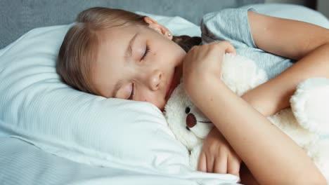 Mädchen-Schläft-In-Einem-Bett-Mit-Teddybär-Und-Lächelt-Zoomend