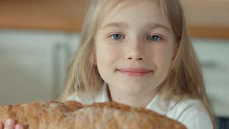 Girl-Smelling-A-Bread-And-Looking-At-Camera