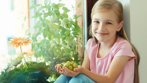 Girl-Smelling-A-Handful-Of-Gooseberry-And-Offers-To-Viewer