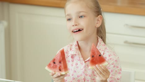 Girl-Sniffing-Watermelon-In-The-Kitchen-And-Smiling-At-The-Camera