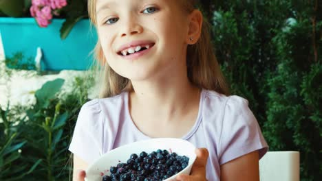 Girl-Sniffing-And-Showing-Bowl-With-Blueberries-At-Camera-Closeup