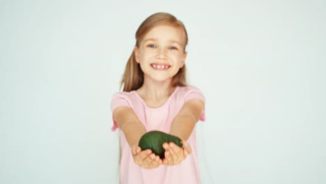Girl-Sniffing-Avocado-And-Showing-It-At-Camera-On-The-White-Background