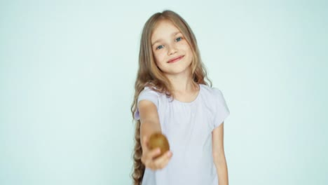 Girl-Sniffing-Kiwi-And-Showing-At-Camera-On-The-White-Background