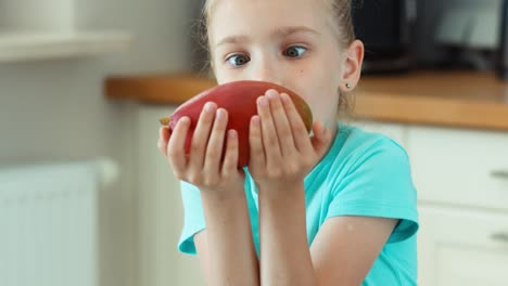 Girl-Sniffing-Mango-And-Laughing-At-Camera-Child-Promotes-Fruit-Mango