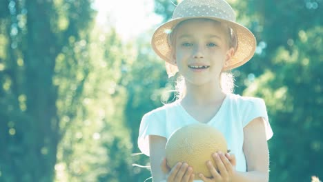 Girl-Sniffing-Melon-And-Smiling-At-Camera-Child-Touting-Melon