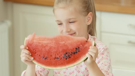 Girl-Sniffing-Watermelon-And-Smiling-At-The-Camera