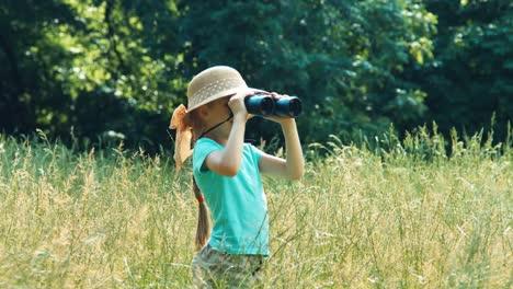 Mädchen-Steht-Im-Hohen-Gras-Und-Schaut-Durch-Ein-Fernglas-In-Entfernung-02