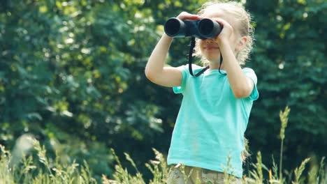Mädchen-Das-Im-Hohen-Gras-Steht-Und-Durch-Ein-Fernglas-In-Entfernung-01-Schaut