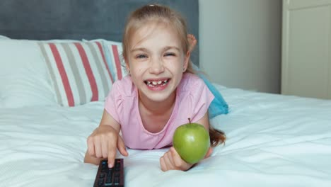 Girl-Switching-Tv-Lying-On-The-Bed-Child-Holding-Green-Apple
