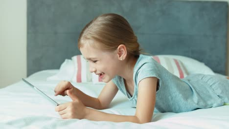 Girl-Using-Playing-Tablet-PC-Child-Lying-On-The-Bed
