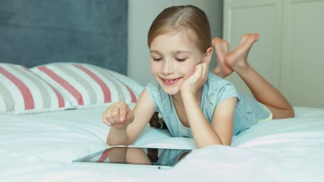Girl-Using-Tablet-PC-Lying-On-The-Bed-And-Laughing-At-Camera-Thumb-Up-Ok