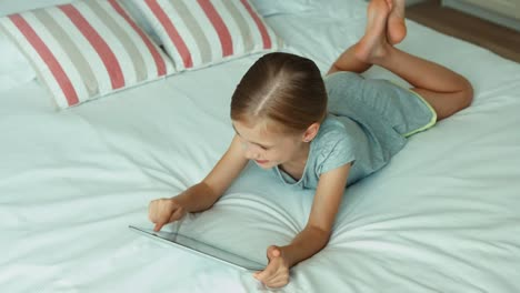Girl-Using-Tablet-PC-Lying-On-The-Bed-And-Laughing-At-Camera-Top-View