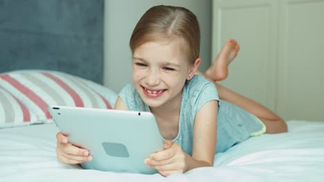 Girl-Using-Tablet-PC-Lying-On-The-Bed-And-Laughing-At-Camera