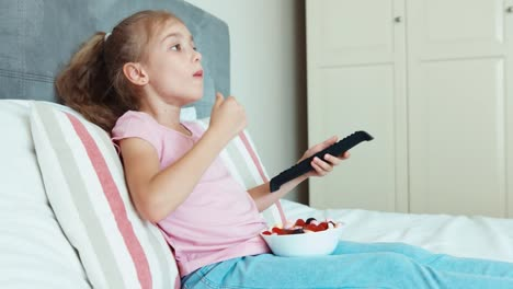 Girl-Watches-Television-Channels-And-Eating-Sweets