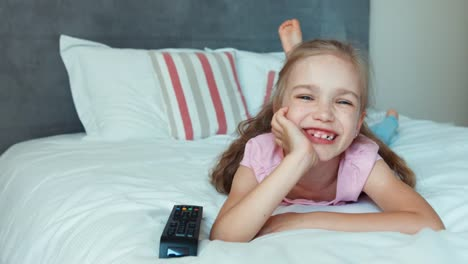 Girl-Watching-Tv-Lying-On-The-Bed-And-Smiling