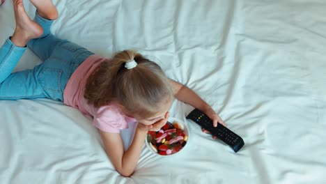 Girl-Watching-Tv-Lying-On-The-Bed-Child-Eating-A-Sweets-Top-View