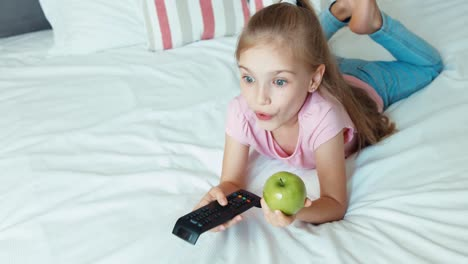 Girl-Watching-Tv-Lying-On-The-Bed-Child-Eating-Apple