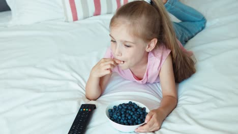 Girl-Watching-Tv-Lying-On-The-Bed-Child-Eating-Blueberries