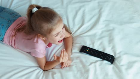 Girl-Watching-Tv-Lying-On-The-Bed-Child-Shocked-Tv-And-Laughing-At-Camera