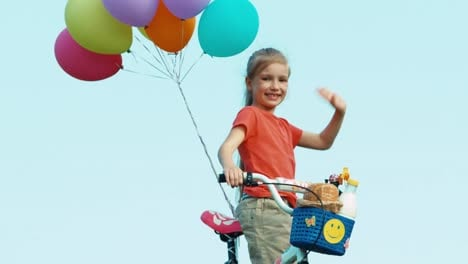 Girl-Waving-Hand-At-Camera-She-Holds-A-Bicycle-With-Balloons-In-The-Basket