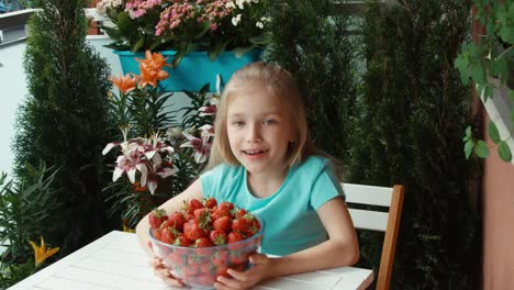 Girl-With-A-Big-Plate-Of-Strawberries-Looking-At-Camera-And-Smiling