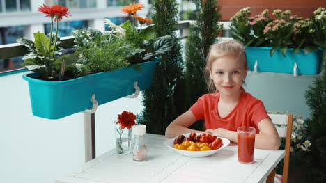 Girl-With-Red-And-Yellow-Cherry-Tomatoes-Looking-And-Smiling-At-Camera