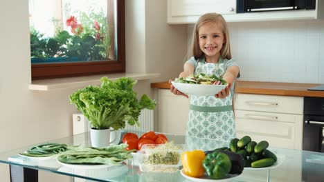 Girl-Young-Chef-Holding-Vegetables-Near-Kitchen-Table-And-Smiling-At-Camera