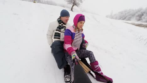 Guy-And-His-Girlfriend-Riding-Down-A-Steep-Hill-On-A-Toboggan