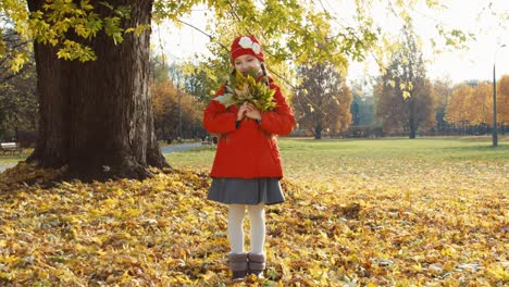 Happy-Niño-Girl-Holding-A-Bouquet-Of-Autumn-Leaves-In-The-Park-And-Smiling-A