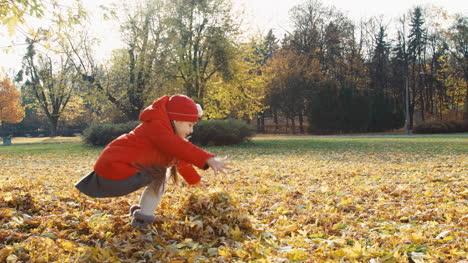 Glückliches-Kindermädchen-Wirft-Herbstlaub-Im-Park-Hoch-und-Lacht-In-Die-Kamera