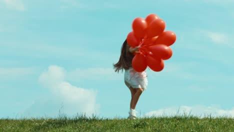 Niño-Feliz-Corriendo-Por-La-Hierba-Niña-Sosteniendo-Grandes-Globos-Rojos