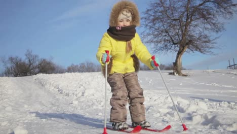 Happy-Cute-Little-Girl-Riding-Down-A-Snow-Hill-On-A-Ski