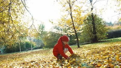 Glückliches-Mädchen-7-Jahre-Alt-Wirft-Im-Herbst-Blätter-Im-Park-und-Lacht