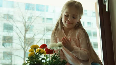Happy-Girl-Admiring-Flowers-And-Sitting-On-The-Windowsill