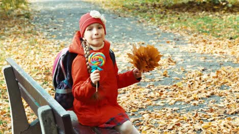 Happy-Girl-Holding-Lollipop-And-Sitting-On-The-Bench-In-The-Park-In-The-Autumn