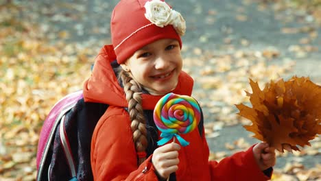Happy-Girl-Licks-Candy-Lollipop-And-Sitting-On-The-Bench-In-The-Park-In-The-A