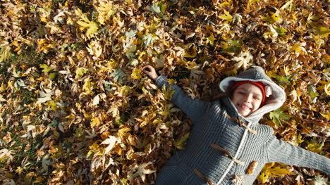 Glückliches-Mädchen-Das-Auf-Den-Herbstblättern-Im-Park-Liegt-und-In-Die-Kamera-Lächelt