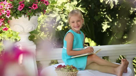 Happy-Girl-Reading-A-Book-And-Waving-Hand-Child-Sitting-On-Table-In-The-Garden