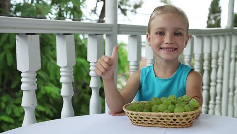 Happy-Girl-With-A-Basket-Of-Grapes-In-The-Table-Shows-Class-And-Smiling