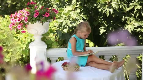 Happy-Little-Girl-Reading-A-Yellow-Book-And-Looking-To-The-Camera-Thumbs-Up