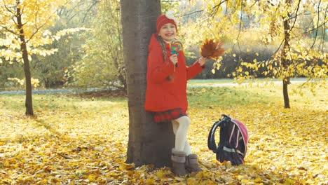 Feliz-Escolar-Niña-Tenencia-Lollipop-Y-Ramo-De-Hojas-Y-Posición-Cerca-árboles