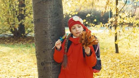 Feliz-Escolar-Niña-Tenencia-Lollipop-Y-Posición-Cerca-árbol-En-El-Parque-Otoño