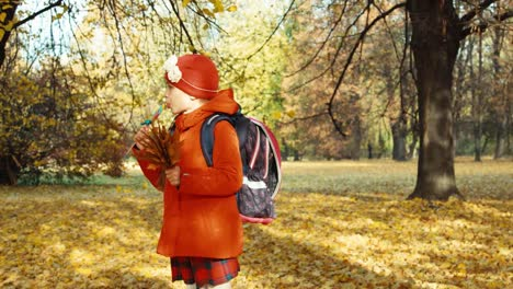 Happy-Schooler-Girl-Holding-Sweets-And-Bouquet-Of-Leafs-In-The-Park-In-Autumn