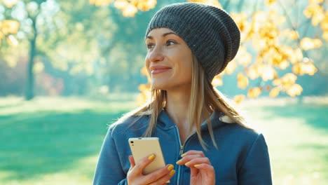 Glückliche-Junge-Blonde-Frau-Mit-Smartphone-Lächelt-In-Die-Kamera-Die-In-Der-Nähe-Von-Bäumen-Steht