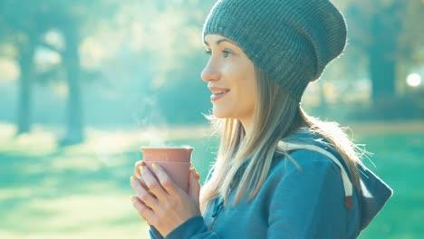 Glückliche-Junge-Frau-Die-Im-Herbst-Tee-Trinkt-Und-Im-Park-In-Die-Kamera-Lächelt