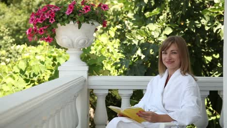 Happy-Young-Woman-Reading-A-Book-While-Sitting-In-Chairs-On-The-Porch