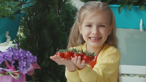 Laughing-Child-Holding-Cherry-Tomatoes-And-Invites-The-Viewer-Zooming