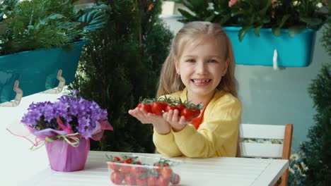 Laughing-Child-Holding-Cherry-Tomatoes-And-Invites-The-Viewer